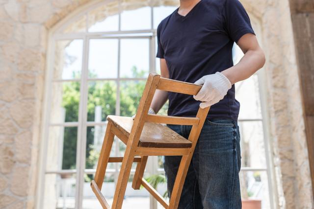 椅子を持つ男性